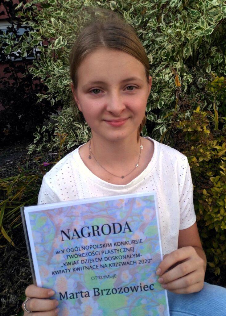 Nagrodzona uczennica prezentująca dyplom za udział w konkursie