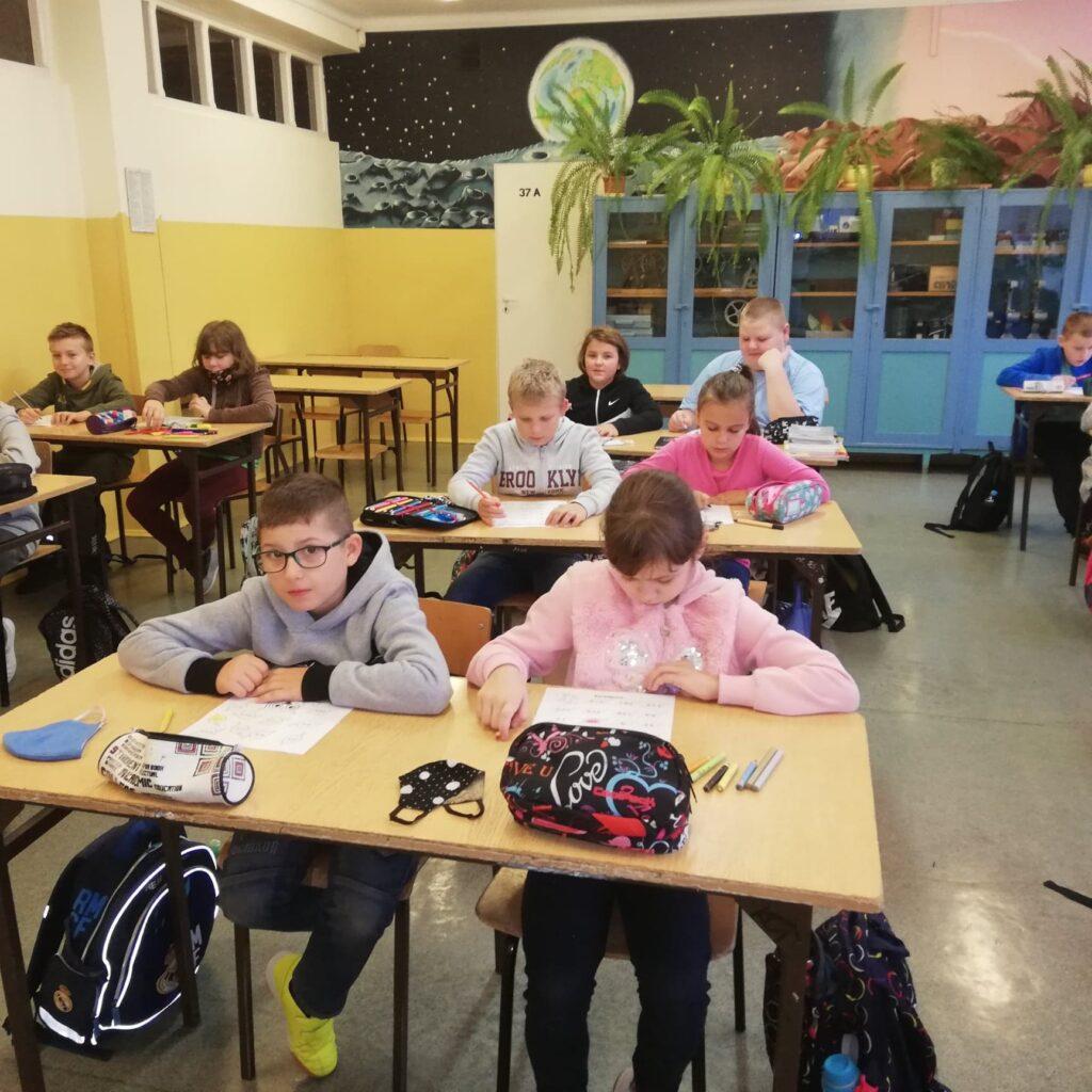 Uczniowie klas IV rozwiązują zadania siedząc w ławkach.