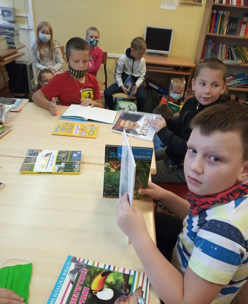 Uczniowie czytający książki w bibliotece szkolnej