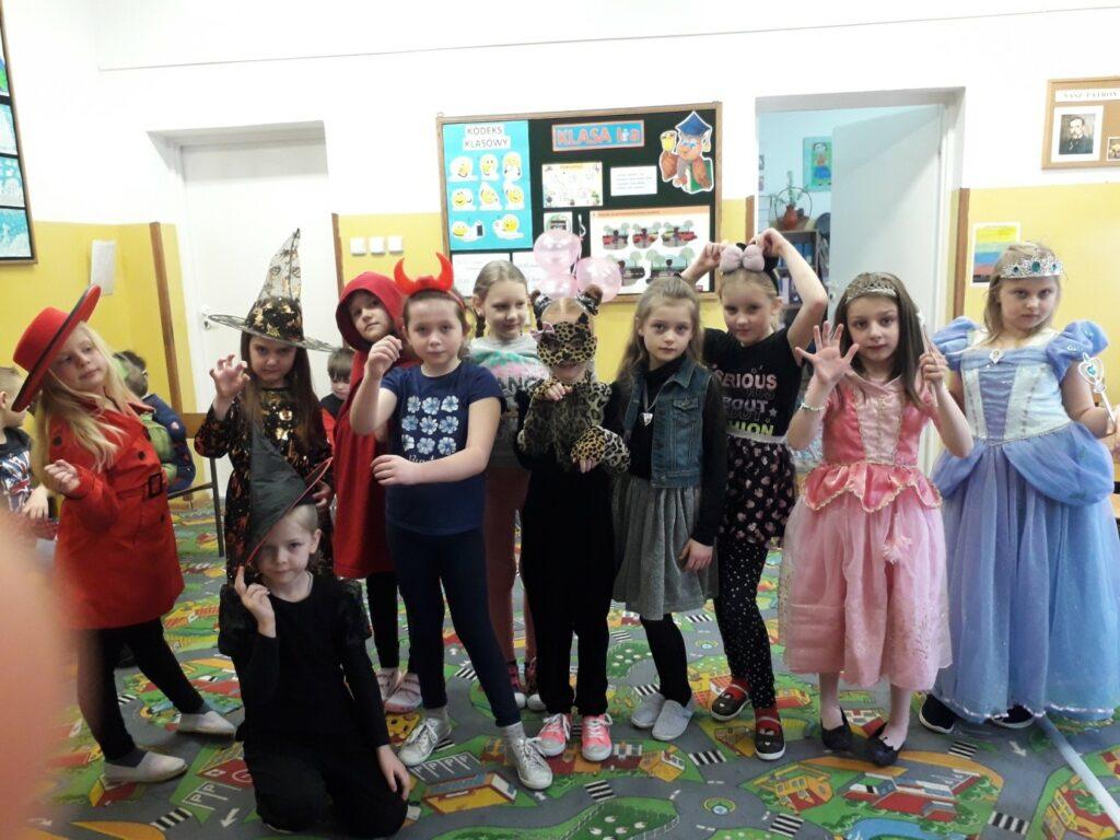 Dziewczynki z klasy I a pozują w strojach karnawałowych wróżek, czarownic, księżniczek, Czerwonego Kapturka, tygryska, złodziejki i Myszki Miki