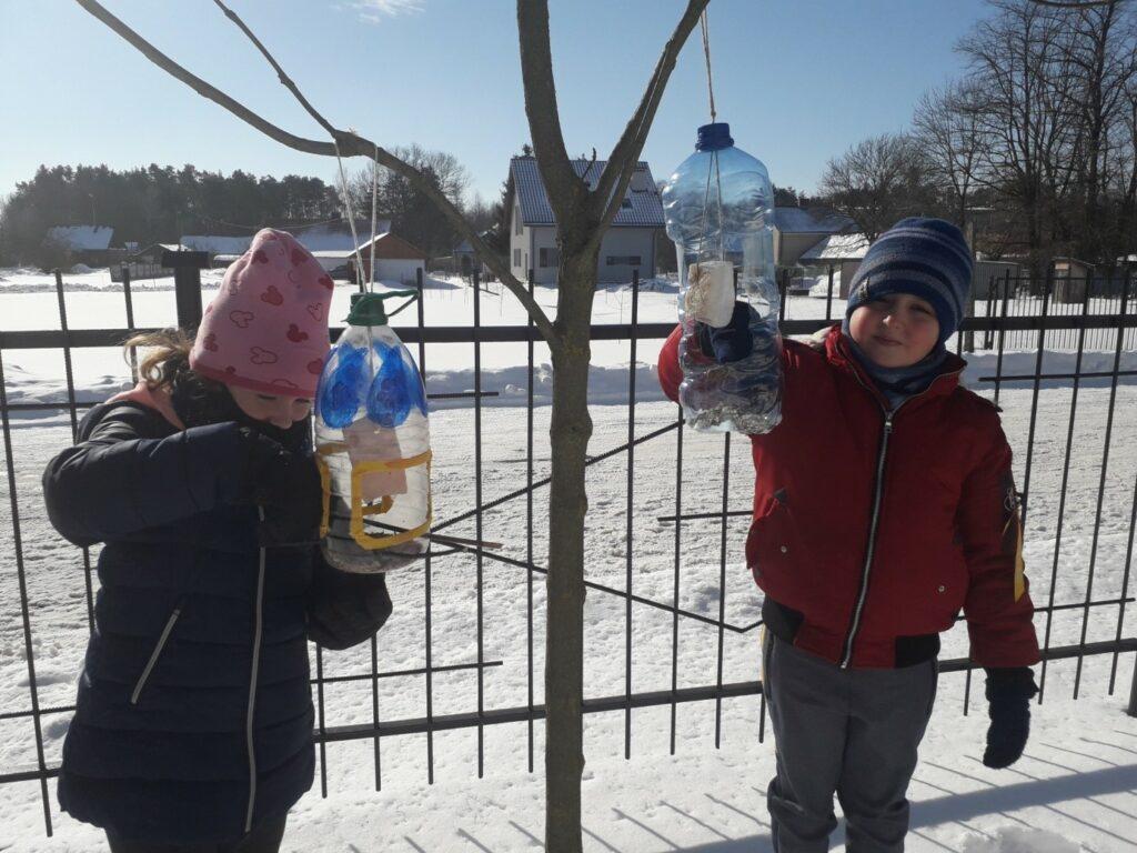 Dwoje uczniów klasy I a wsypuje do karmników ziarna i zawiesza w nich słoninki