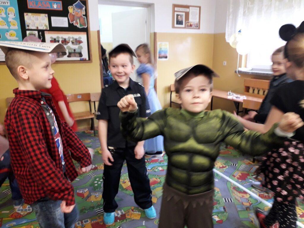 Trzech uczniów klasy I a rywalizuje w tańcu z gazetą na głowie.