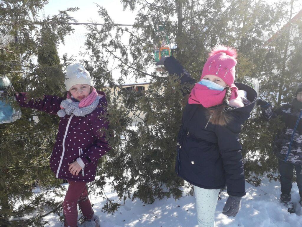 Dwie dziewczynki zawieszają na tujach swoje karmniki