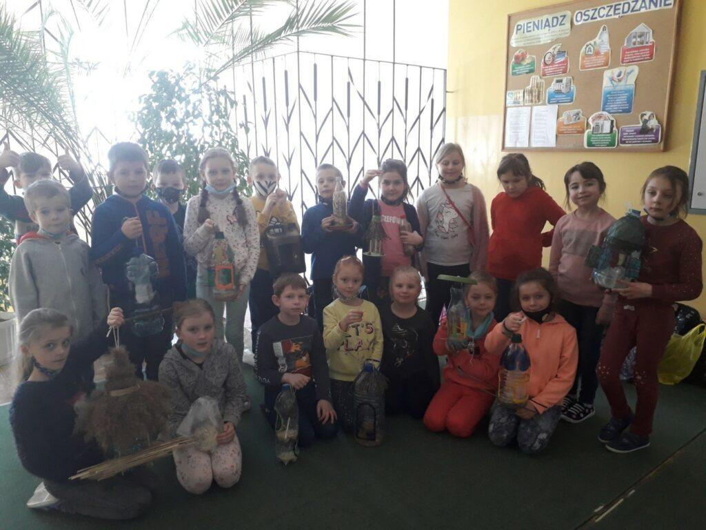 Uczniowie klasy I a prezentują wykonane z recyklingu karmniki