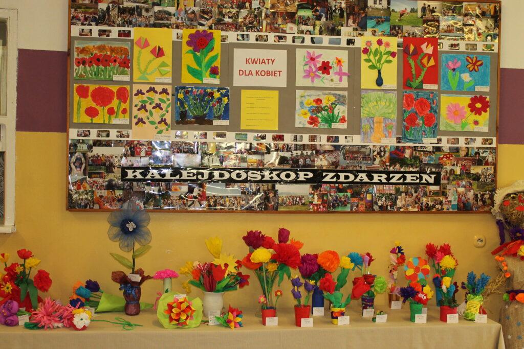 Prace plastyczne uczniów wykonane na konkurs Kwiaty dla Kobiet. Są piękne, kolorowe duże i małe, barwne, wiosenne w swoim wyglądzie. Ustawione są na stoliku aby bardziej były widoczne z każdej strony