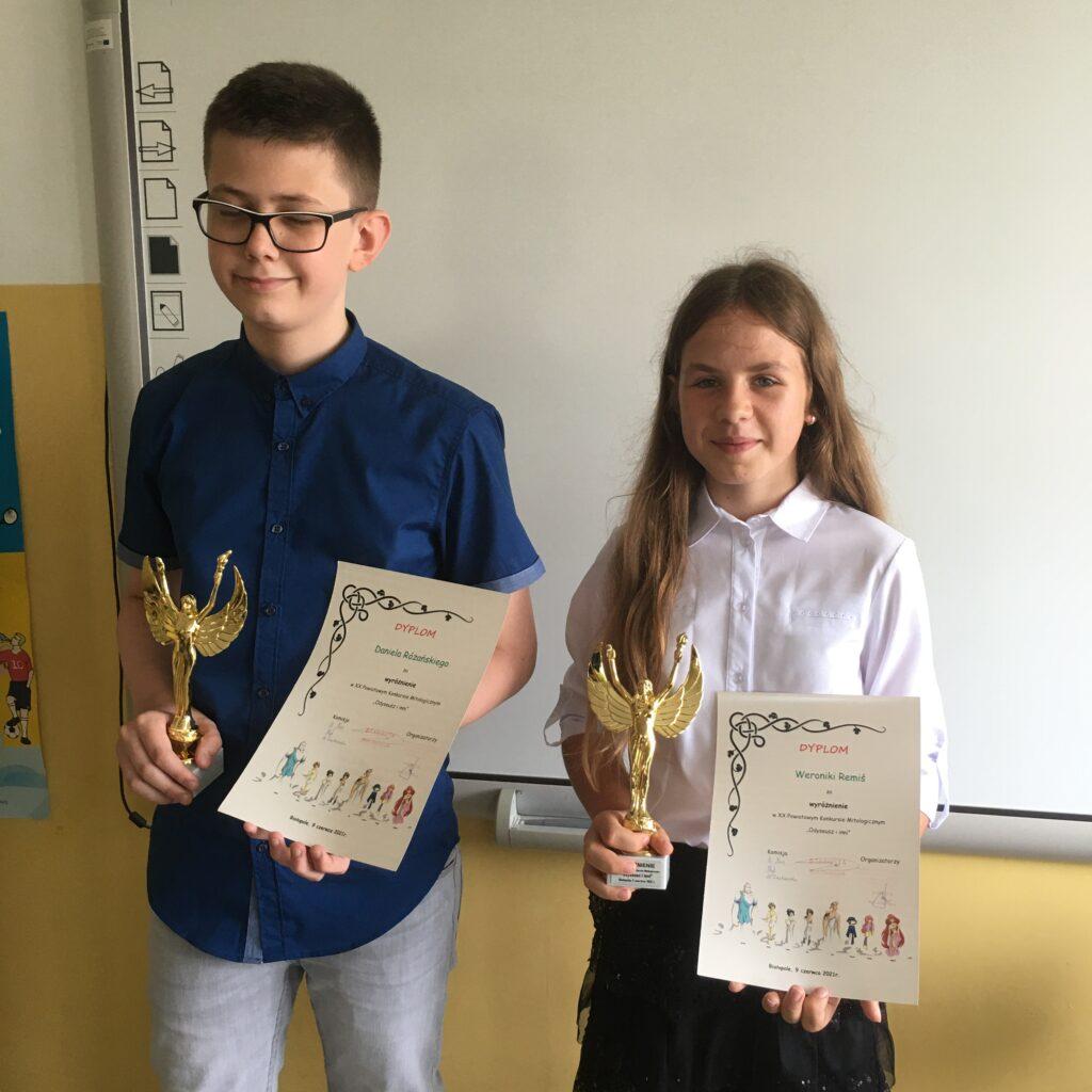 Dwoje uczniów trzyma statuetki oraz dyplomy.